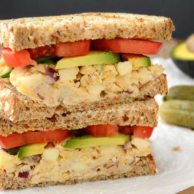 Apple walnut chickpea salad sandwich topped with avocado and tomato cut in half and stacked.