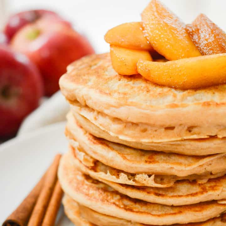 A stack of vegan pancakes topped with cinnamon apples.