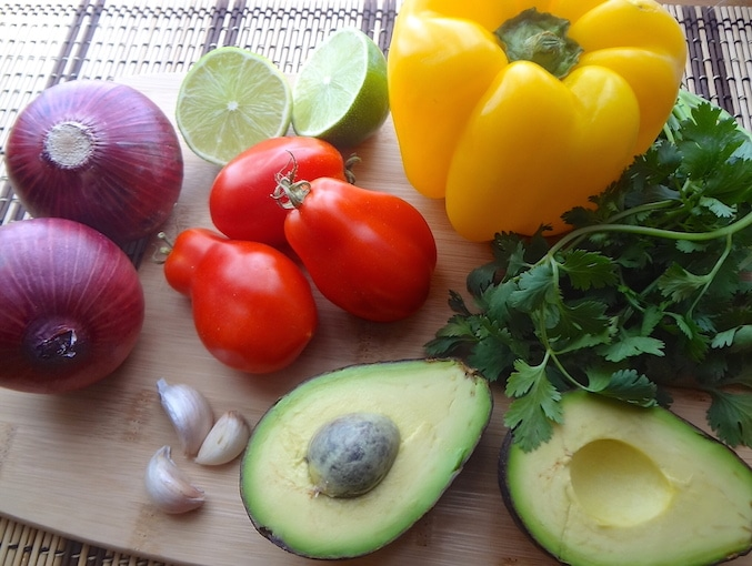 Potato Tacos ingredients photo. 2 whole red onions, a lime sliced in half, 3 garlic cloves, 3 roma tomatoes, a yellow bell pepper, an avocado cut in half and a fresh bunch of cilantro on a bamboo cutting board.