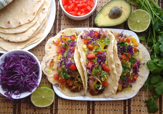 A top angle of 3 plated vegan potato tacos on a tan and brown mat. They're filled with seasoned refried beans, adobo seasoned potatoes, fajita style bell peppers and onions, fresh shredded purple cabbage and lettuce, cilantro leaves and diced tomatoes. Around the potato tacos sits a lime wedge, bowl of purple cabbage, plate of fresh homemade tortillas, a bowl of fresh diced tomatoes, half an avocado, and fresh cilantro.
