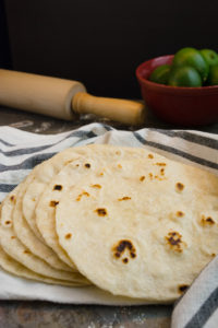 A stack of homemade flour tortillas on a towel.
