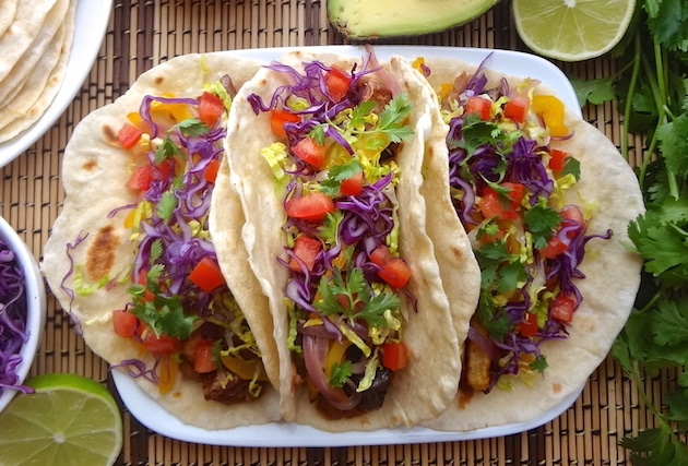A close up top angle of 3 plated vegan potato tacos on a tan and brown mat. They're filled with seasoned refried beans, adobo seasoned potatoes, fajita style bell peppers and onions, fresh shredded purple cabbage and lettuce, and tomatoes. Around the potato tacos sits a lime wedge, bowl of purple cabbage, plate of fresh homemade tortillas, half an avocado, and fresh cilantro.