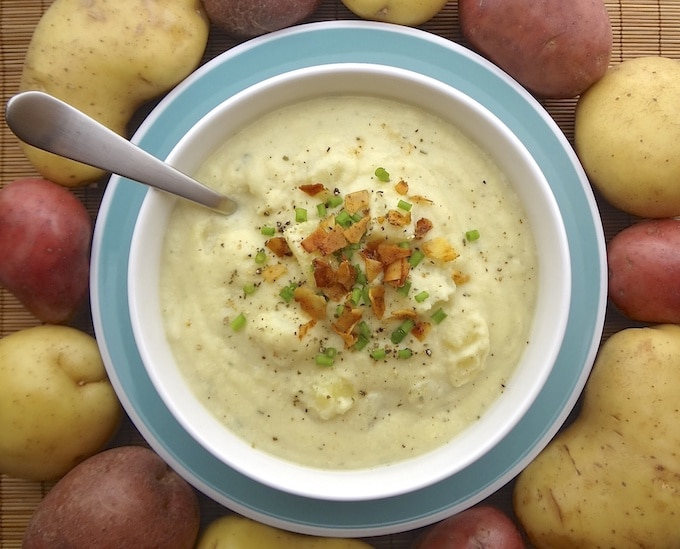 Vegan creamy potato cauliflower soup topped with coconut bacon and green onions.