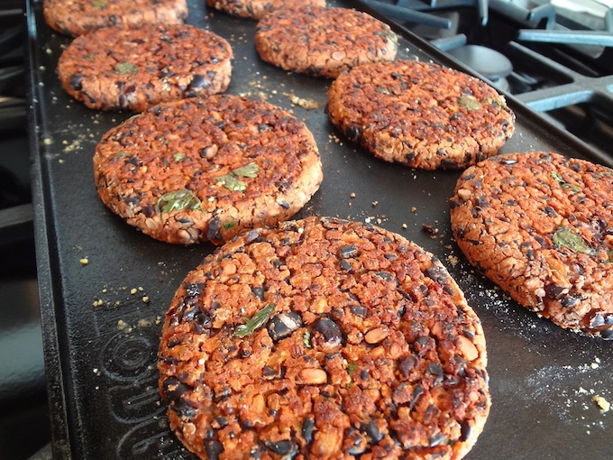 No crumble black bean burgers cooking on the grill.