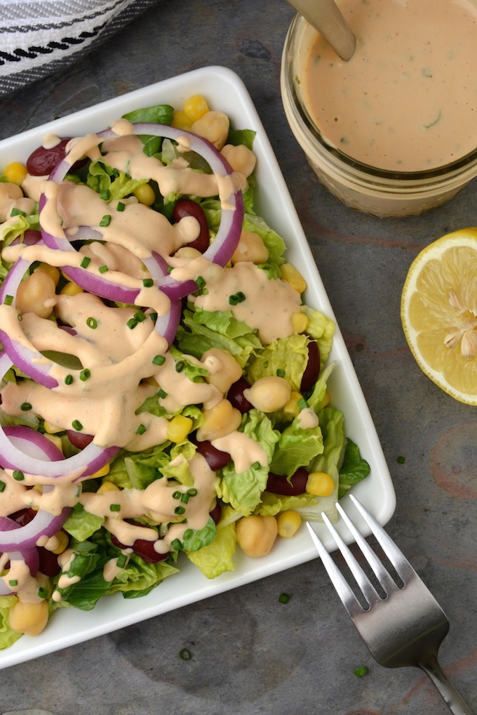 A salad topped with red onion rings, garbanzo beans, kidney beans, corn and creamy vegan BBQ Ranch Dressing with a jar of the dressing on the side.