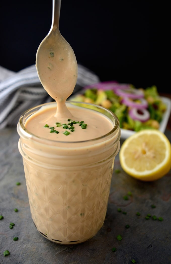 A jar of Creamy Vegan BBQ Ranch Dressing with a spoon covered in dressing being lifted out.