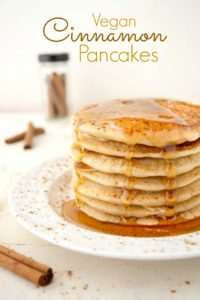Stack of vegan cinnamon pancakes with maple syrup dripping down.