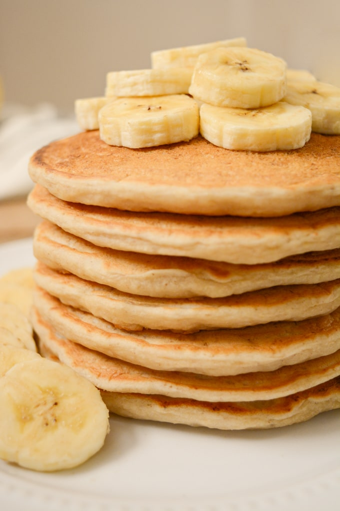 A stack of vegan banana milk pancakes topped with banana slices on a white plate.