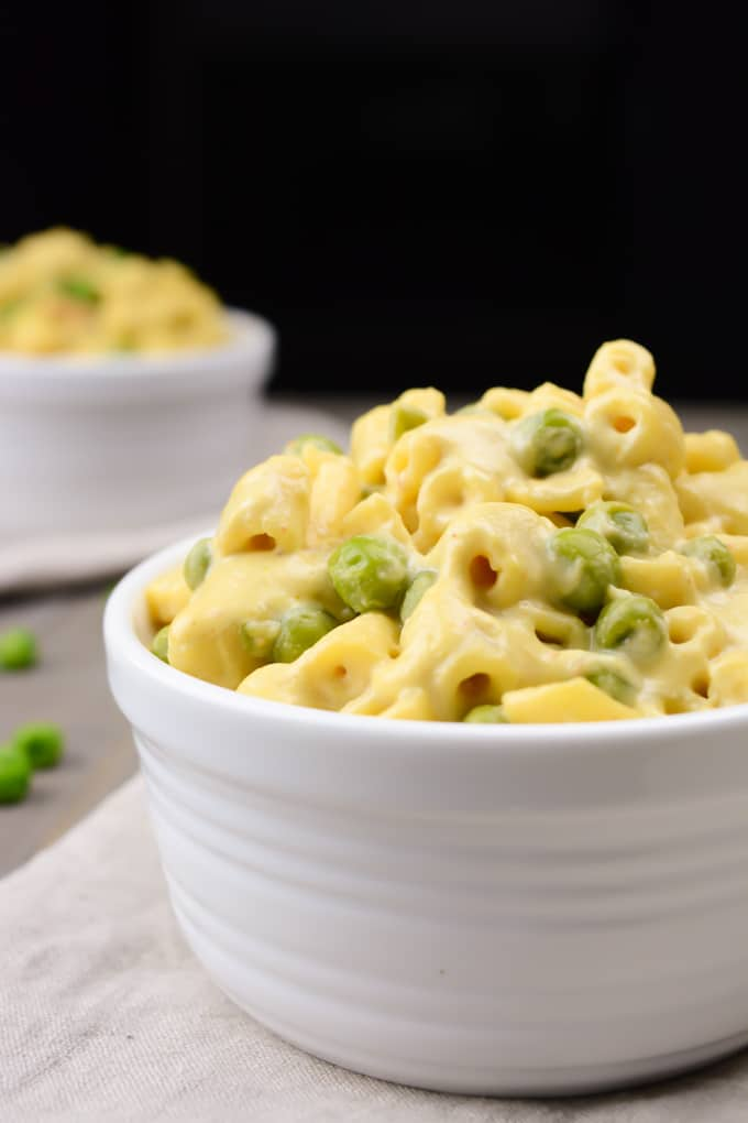 Creamy vegan mac and cheese with peas in a white bowl.