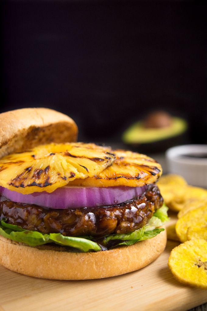 Grilled huli-huli vegan burger topped with red onion and grilled pineapple rings.