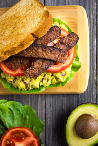 Vegan BLT Sandwich topped with avocado chickpea mash and tempeh bacon.