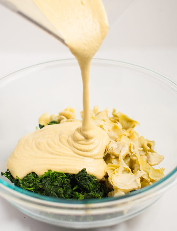 Cashew sauce being poured over spinach and artichoke hearts for vegan spinach artichoke dip.