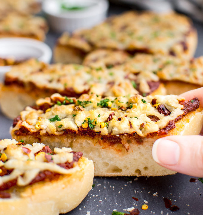 A slice of cheesy vegan french bread pizza being grabbed.