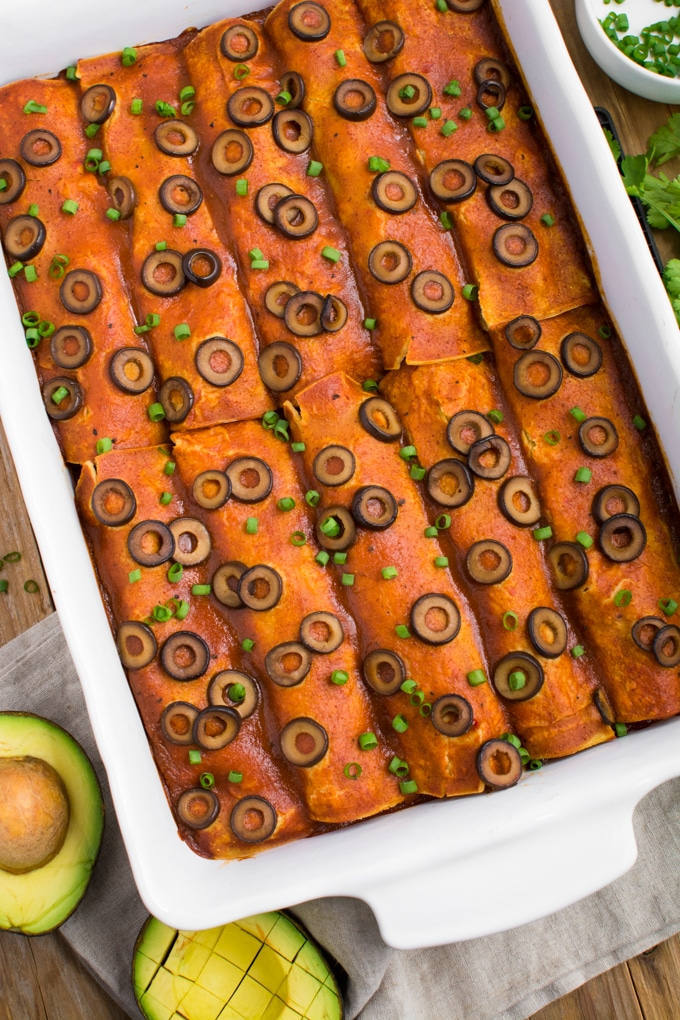 Cooked black bean enchiladas in a white dish ready topped with sliced olives and green onions.