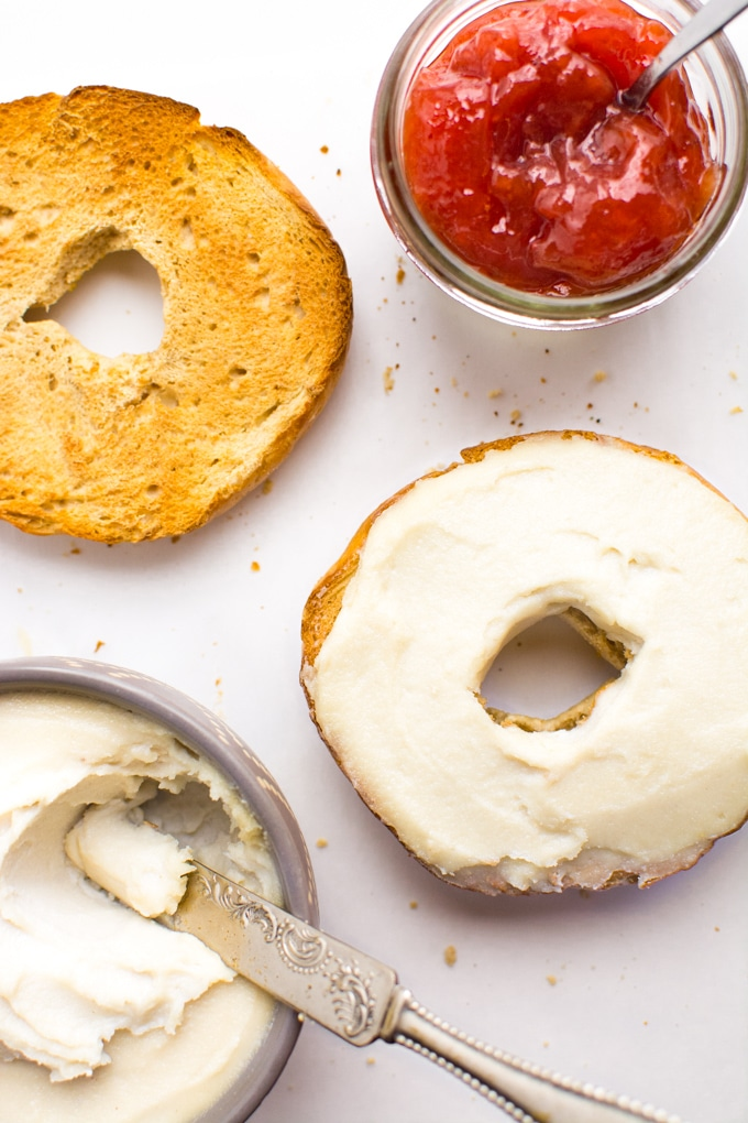 Cashew cream cheese spread on half a toasted bagel with a side of strawberry preserves.