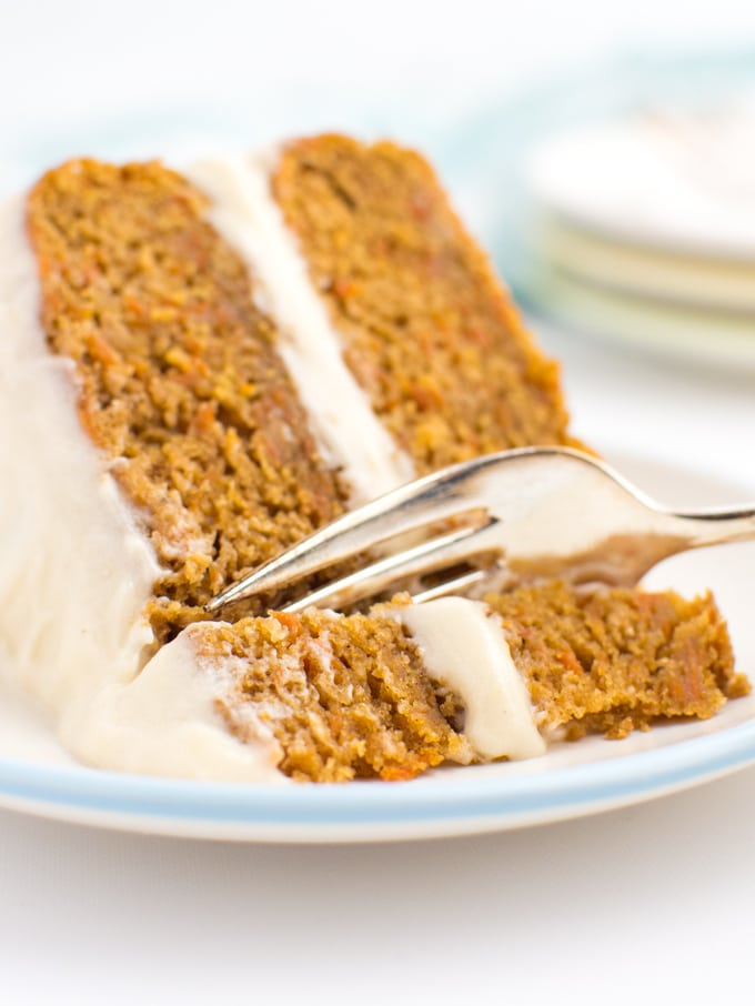 A slice of carrot cake with a fork cutting into it.