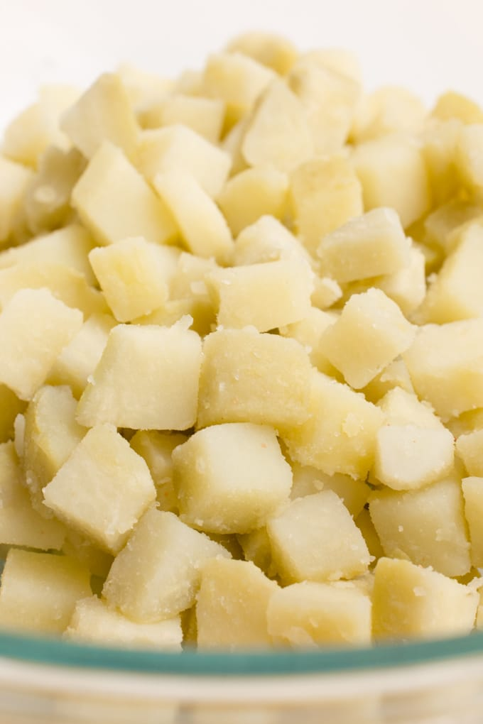 A glass bowl of diced boiled potatoes.