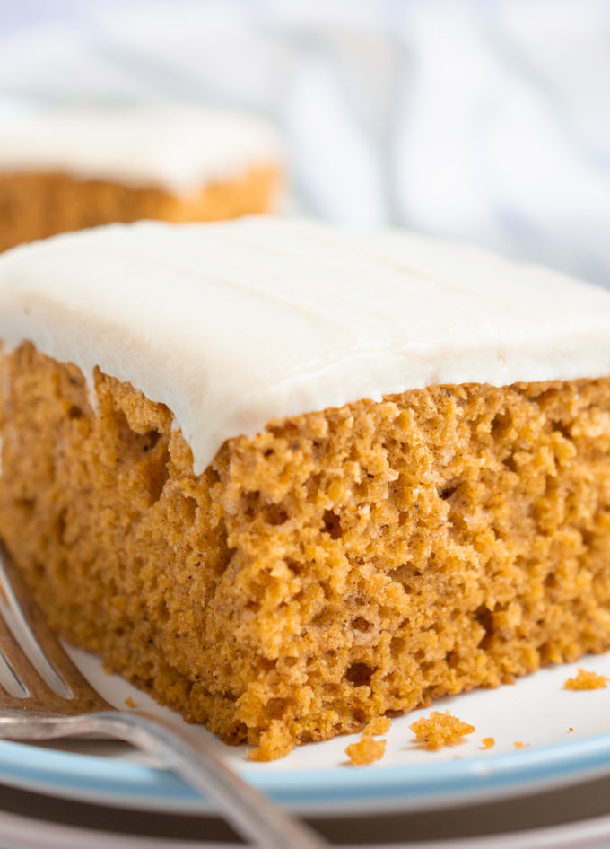 A slice of vegan pumpkin cake topped with cashew cream frosting on a white plate.