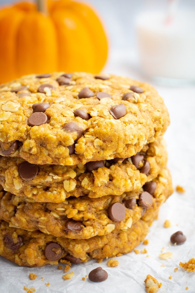 A sack of vegan pumpkin oatmeal cookies with chocolate chips, a glass of almond milk, and an orange pumpkin.