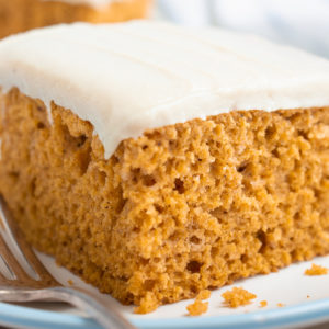 A slice of vegan pumpkin cake on a white plate with a fork.