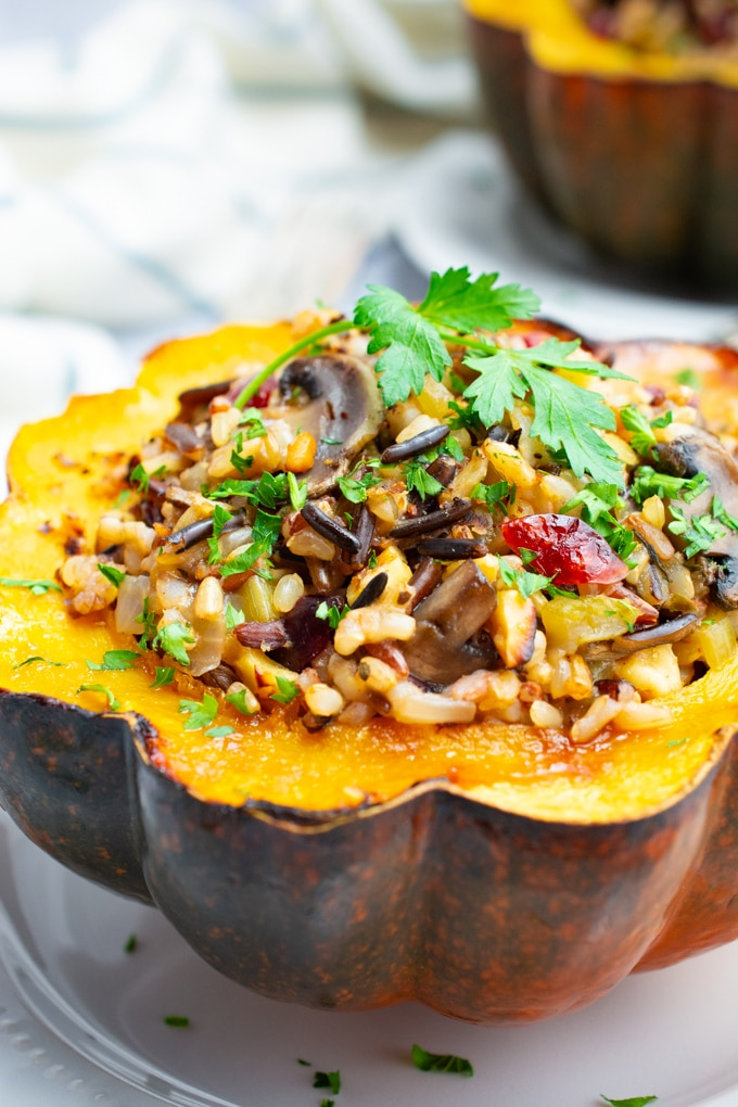 Vegan wild rice stuffed acorn squash topped with a fresh parsley leaf.