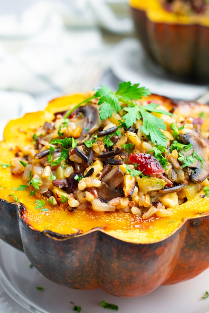 Vegetarian stuffed acorn squash filled with wild rice on a white plate