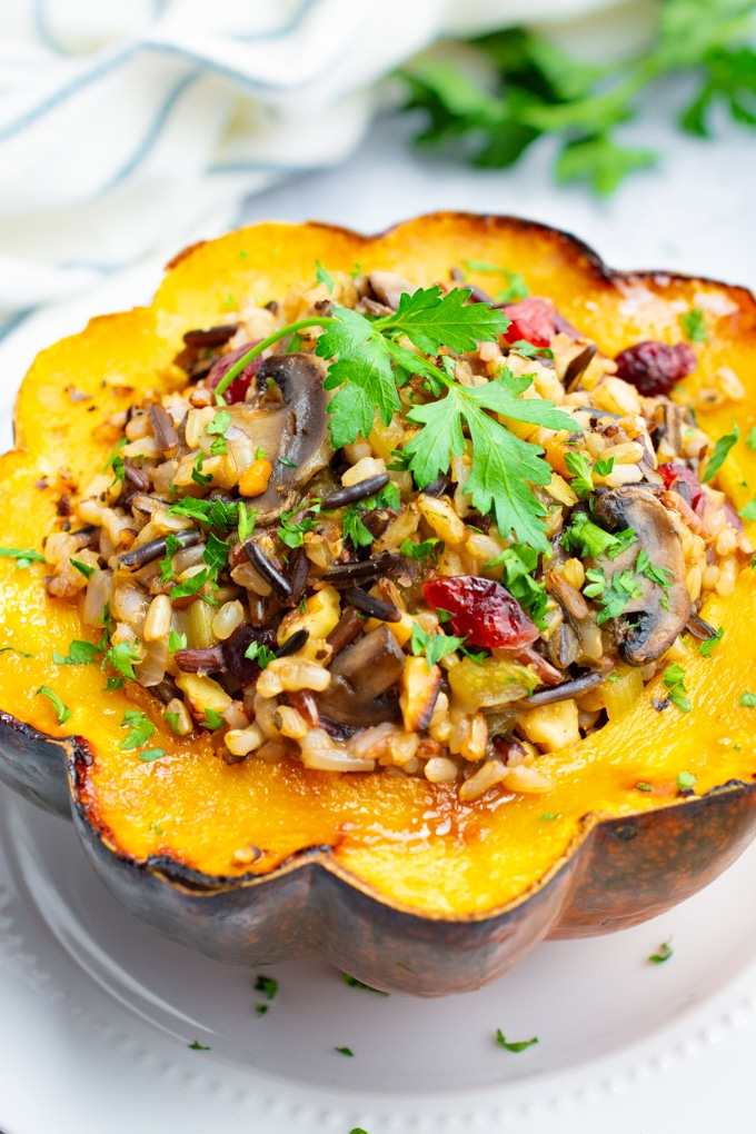 Flower shaped wild rice stuffed acorn squash on a white plate.