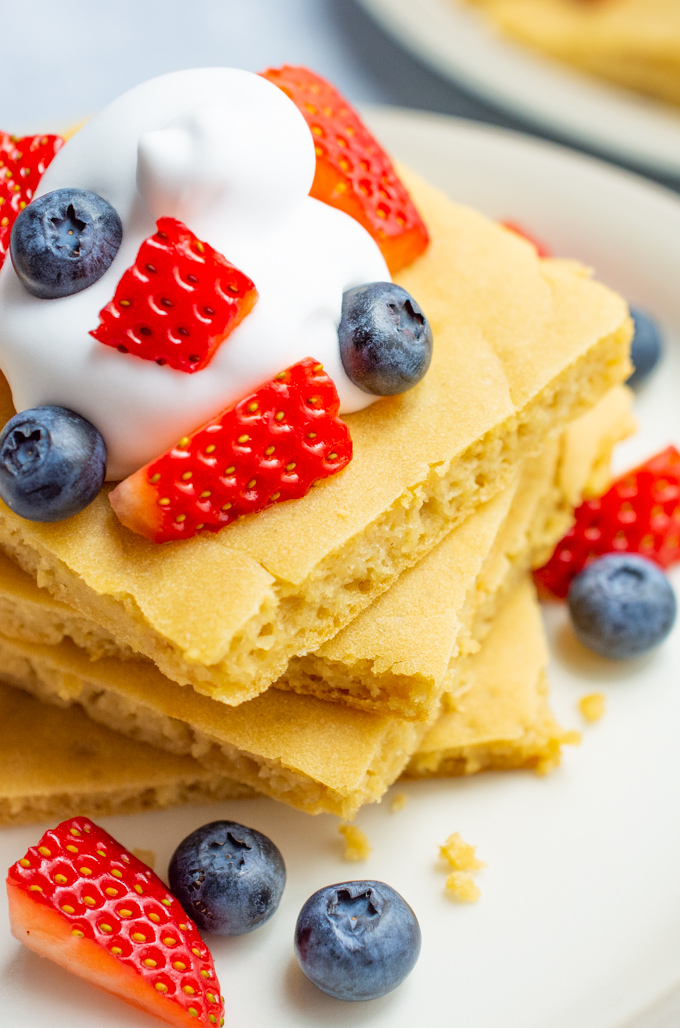 A stack of square pancakes with fruit and whip.