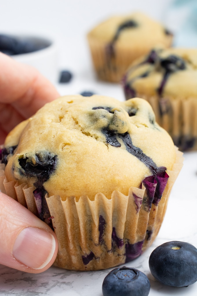 A hand grabbing a blueberry muffin.