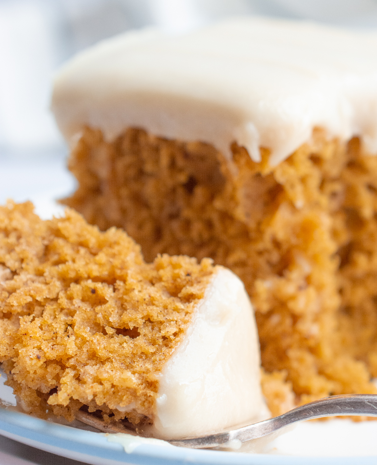 A bite of vegan pumpkin cake with frosting on a fork.